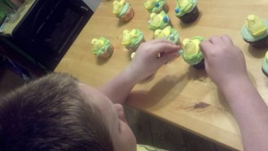 David putting 'robin eggs' on cupcakes